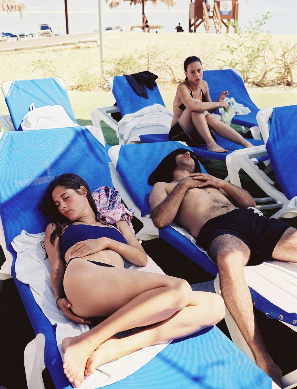 Film photography by Dina Goldstein shot at a Dead Sea resort, Israel. Includes images of sun bathers and people in the Dead Sea ocean.