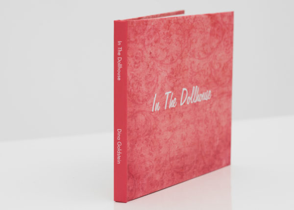 n The Dollhouse hard cover signed book by Dina Goldstein. A collection of essays, published pieces, interviews, production secrets and anecdotes about the In the Dollhouse series.